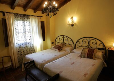 Camas de la habitación Águila. También se ve el banco a los pies de las camas, un sillón, la mesita de noche y la ventana