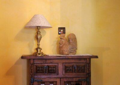 Armarito decorativo con una lámpara y una escultura de un gallo como decoración