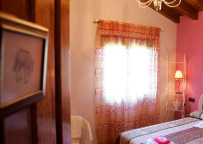 Entrada a habitación Lobo Rosa, vista de la cama y ventana